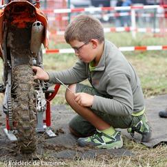 Un jeune mécano travaille sur sa moto avant la mini Chinelle.